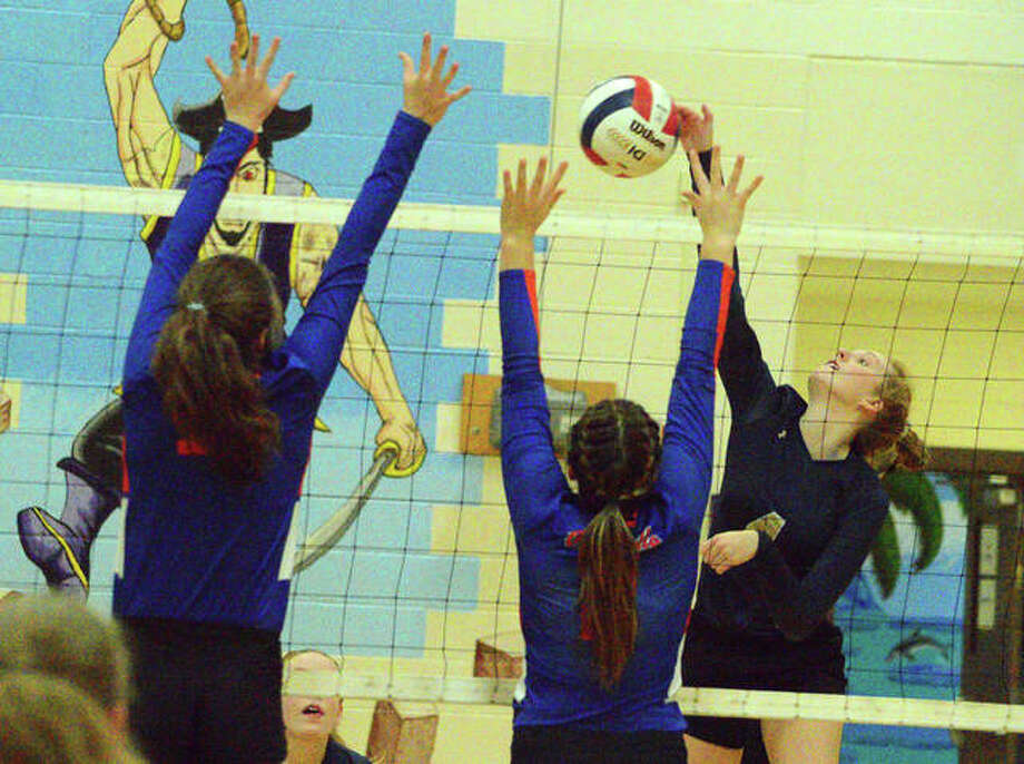 Father McGivney's Anna McKee, right, tries to hit over a pair of Okawville blockers during Wednesday's semifinal match at the Class 1A Valmeyer Regional. Photo: Scott Marion/The Intelligencer