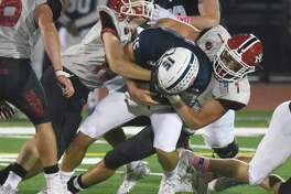 New Canaan's Chris Carratu (1) and Jack Hagan (19) tackle Staples' Jake Thaw (15) during a football game in Westport on Friday, Oct. 25, 2019.