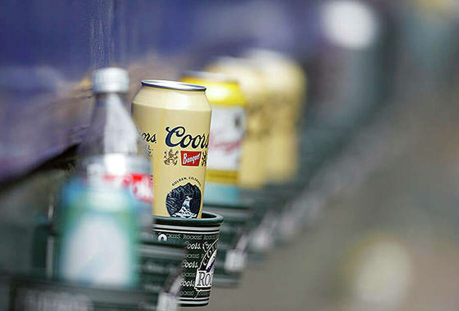 Empty cans of Coors beer sit in beverage holders on the backs of box seats after the ninth inning of a baseball game. Molson Coors Brewing Co. is laying off 500 workers worldwide and restructuring its operations as it faces declining beer sales. Photo: David Zalubowski | AP