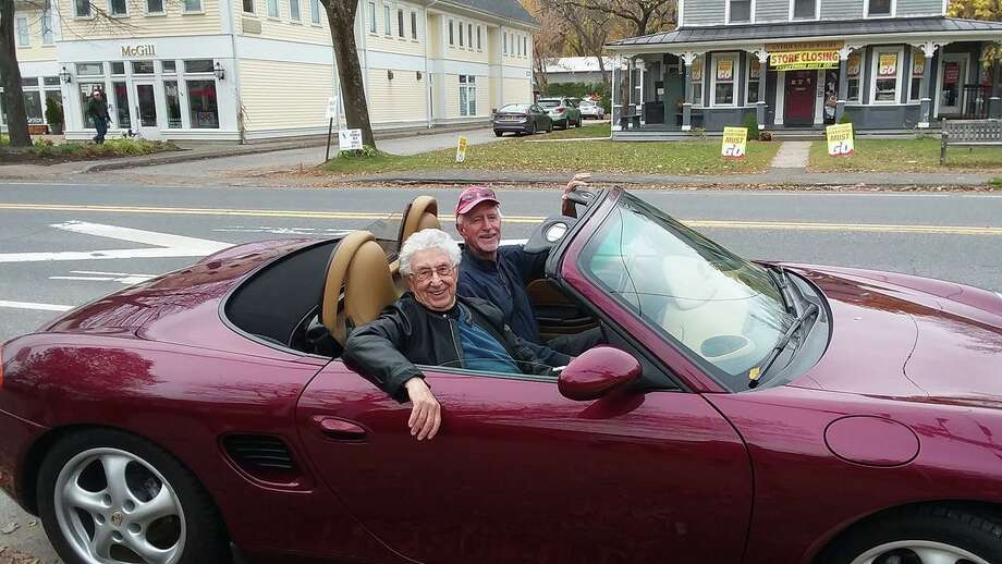 Raffle-winner Ned Babbitt behind the wheel of his new Porsche, joined by Rudy Molho in the passenger seat. Photo: Kent Memorial Library