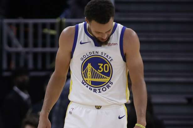 Golden State Warriors' Stephen Curry looks at his left hand after Phoenix Suns' Aron Baynes fell onto him during the second half of an NBA basketball game Wednesday, Oct. 30, 2019, in San Francisco. Curry left the game. (AP Photo/Ben Margot)