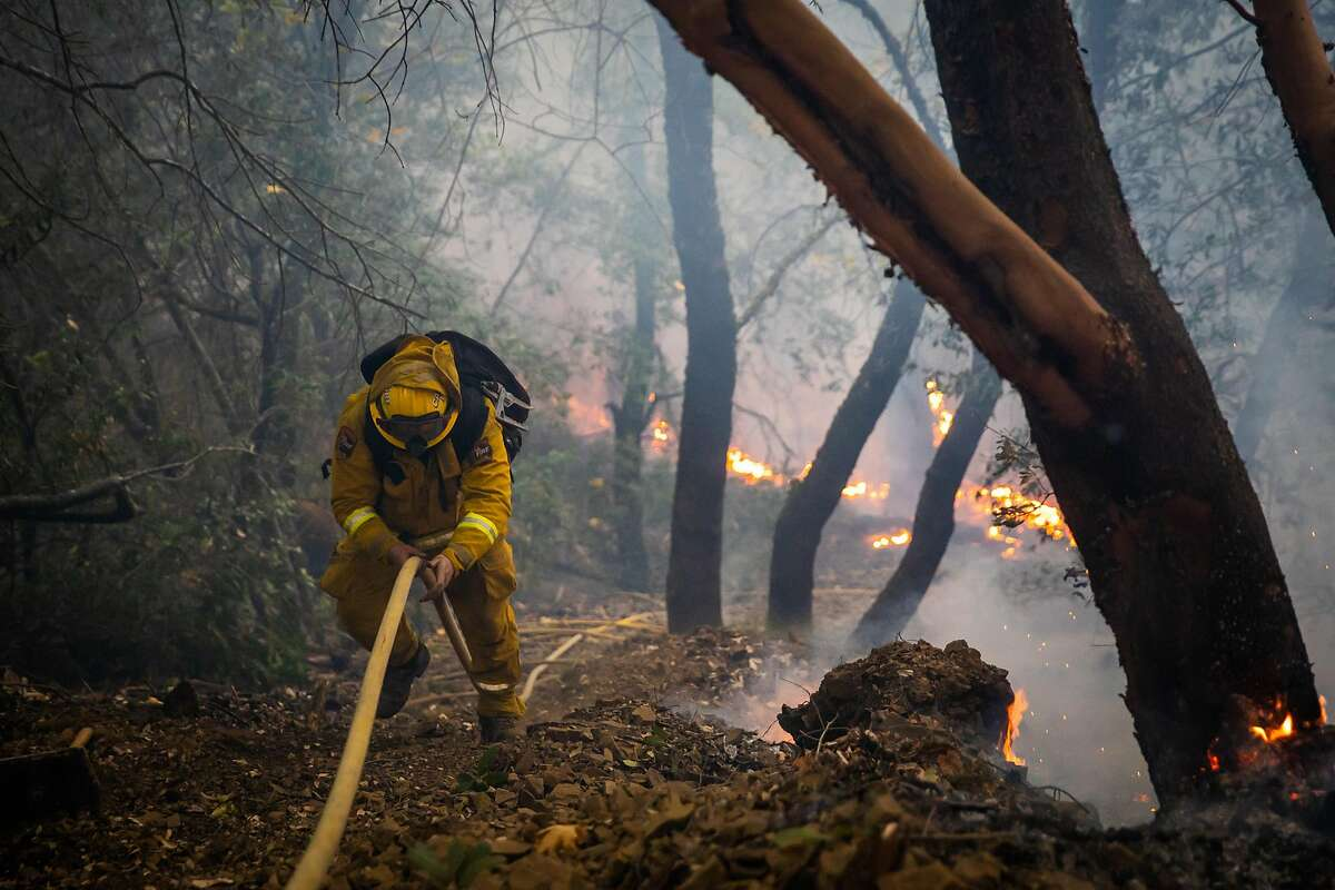A firefighter climbs up a steep containment line on the Kincade fire in Kellogg, Calif. on Wednesday, Oct. 30, 2019.