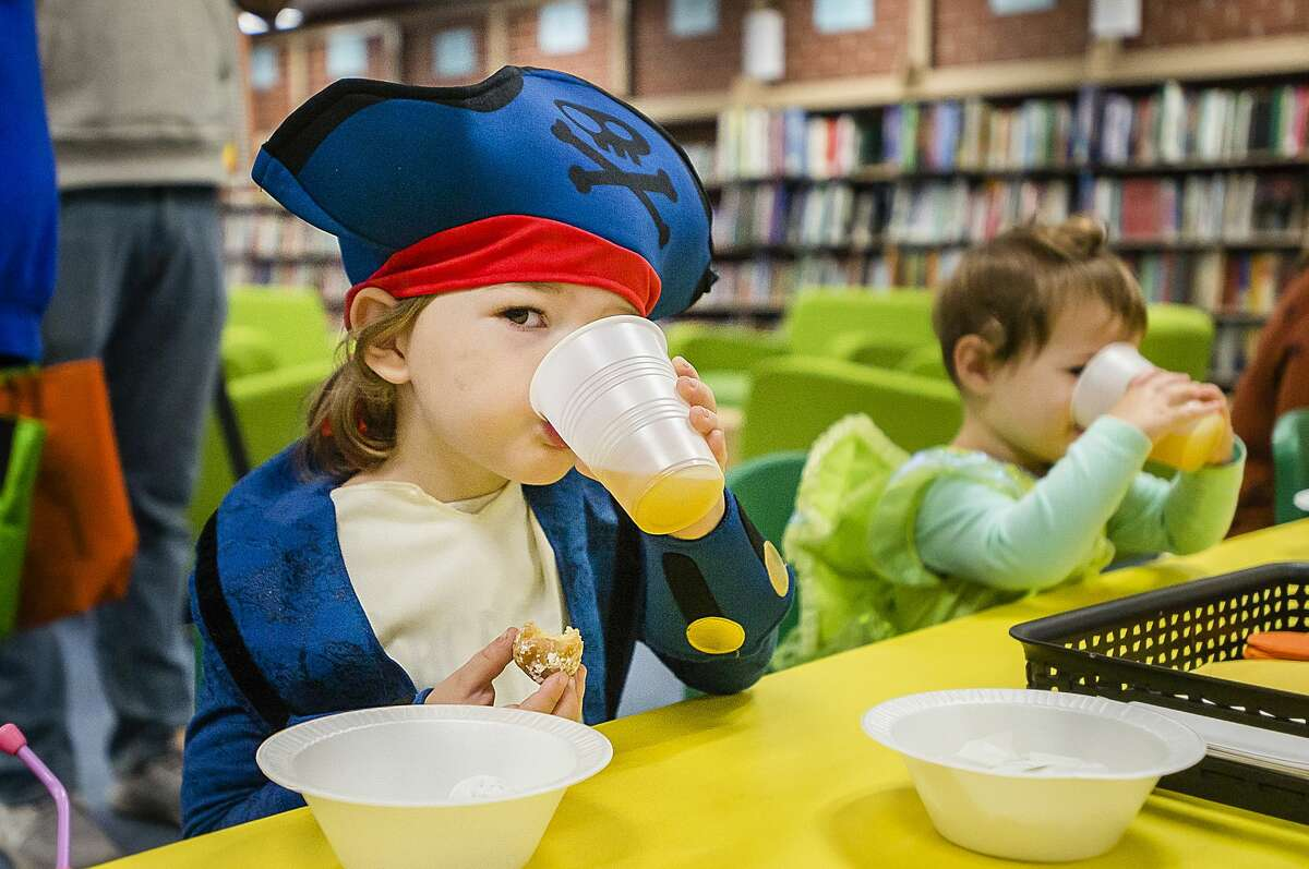 Foster Stinson of MIdland, 3, takes a sip of cider Thursday, Oct. 31, 2019 at Grace A. Dow Memorial Library. (Katy Kildee/kkildee@mdn.net)