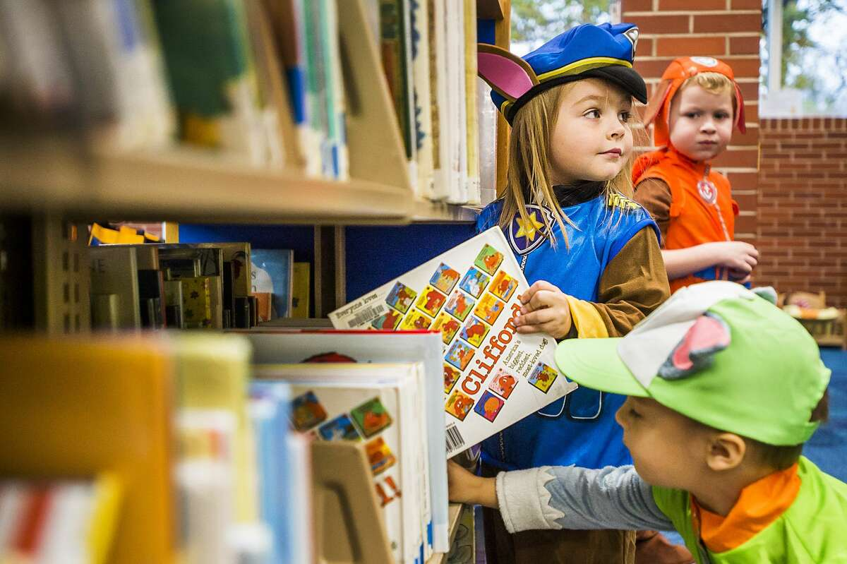 Lois Wilcox, 4, center, and Hank Wilcox, 2, bottom right, dressed as Paw Patrol characters, pick out library books Thursday, Oct. 31, 2019 at Grace A. Dow Memorial Library. (Katy Kildee/kkildee@mdn.net)