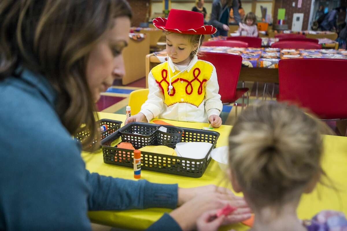 Adalyn Cronkright of Midland, 3, works on a craft in her Halloween costume Thursday, Oct. 31, 2019 at Grace A. Dow Memorial Library. (Katy Kildee/kkildee@mdn.net)