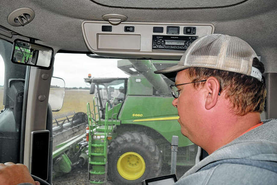 Ryan Boston drives a tractor and waits to collect the harvested soybeans. Photo: Samantha McDaniel-Ogletree | Journal-Courier
