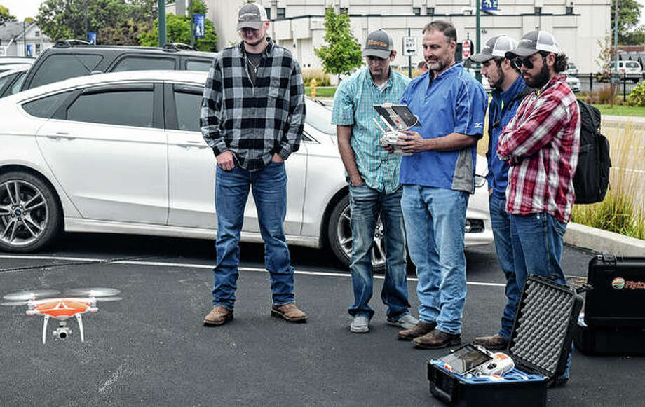 Lincoln Land Community College students Cade Vanausdall (from left) of Virden, Colton Westen of Latham, agriculture professor Rich Teeter, John Sudduth of Sherman and Kaleb Millburg of Raymond take part in a demonstration of a drone at Lincoln Land Community College's Jacksonville location. The drone took pictures of solar panels. Agriculture programs at colleges have adapted to address new technology that has changed the industry. Photo: Marco Cartolano | Journal-Courier