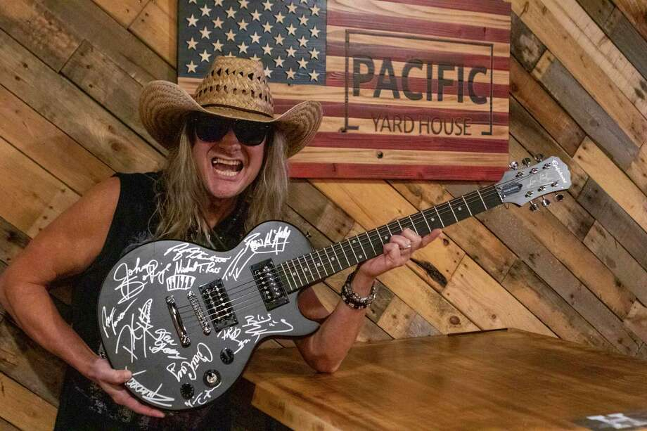 Musician Johnny Solinger, former lead vocalist for the band Skid Row, poses at Pacific Yardhouse in Conroe, with a guitar signed by rock and roll greats. It's his hope to auction off the guitar for charity. Solinger will perform a special Veteran's Day show at Pacific Yardhouse on Monday, Nov. 11, at 5 p.m. Admission is $10, free admission for veterans. Visit http://pacificyardhouse.com/ or johnnysolinger.com for more. Photo: Cody Bahn, Houston Chronicle / Staff Photographer / © 2019 Houston Chronicle
