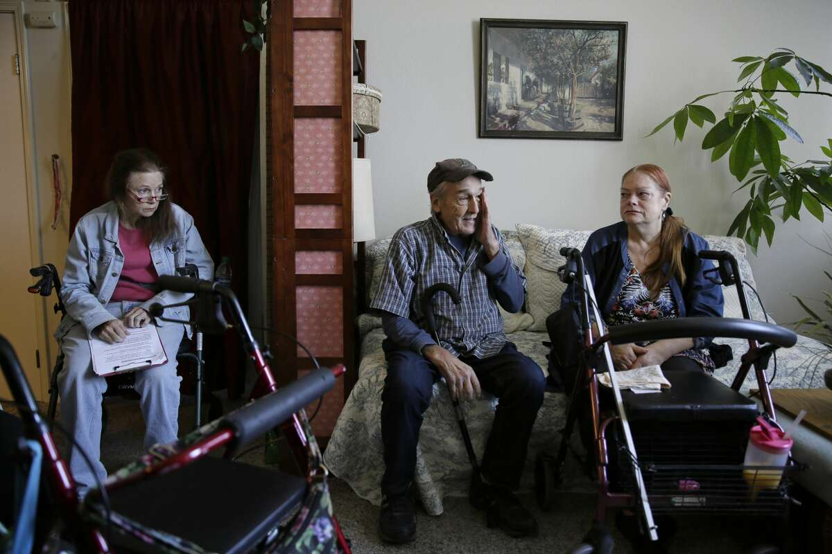 From left, Sharon Wagner-Higgins, Brian Cherry and Theresa Metzger talk about their experiences of being stranded in the dark during the power blackouts at the Villas at Hamilton housing complex for low income seniors Wednesday, Oct. 30, 2019, in Novato, Calif. Pacific Gas & Electric officials said they understood the hardships caused by the blackouts but insisted they were necessary. (AP Photo/Eric Risberg)