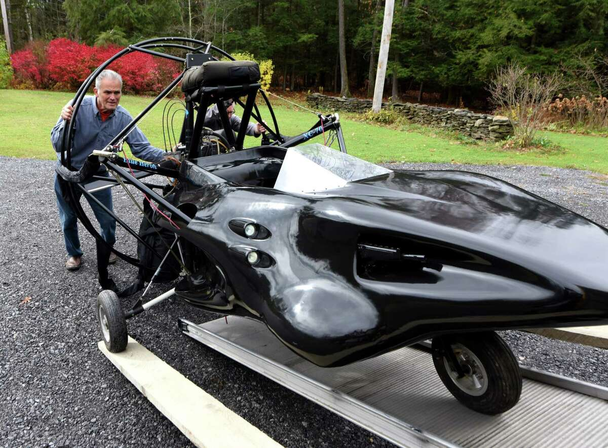 """Nick Viscio, left, helps Dan Treado, assistant curator from the International Spy Museum, load a """"villainous Parahawk"""" from the James Bond film """"The World is Not Enough,"""" which is owned by Viscio on Thursday, Oct. 31, 2019, in Knox, N.Y. Treado is taking the former movie prop to D.C., where it will be displayed in the museum. (Will Waldron/Times Union)"""