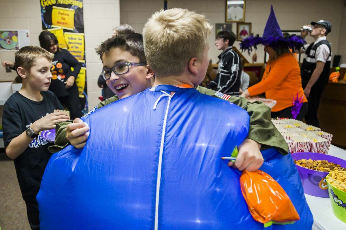 Representatives of businesses in downtown Midland pass out Halloween candy at St. Brigid Catholic School Thursday, Oct. 31, 2019. Each year, St. Brigid students go trick-or-treating through downtown in their costumes, but a steady rain prevented the outdoor parade this year. (Katy Kildee/kkildee@mdn.net)