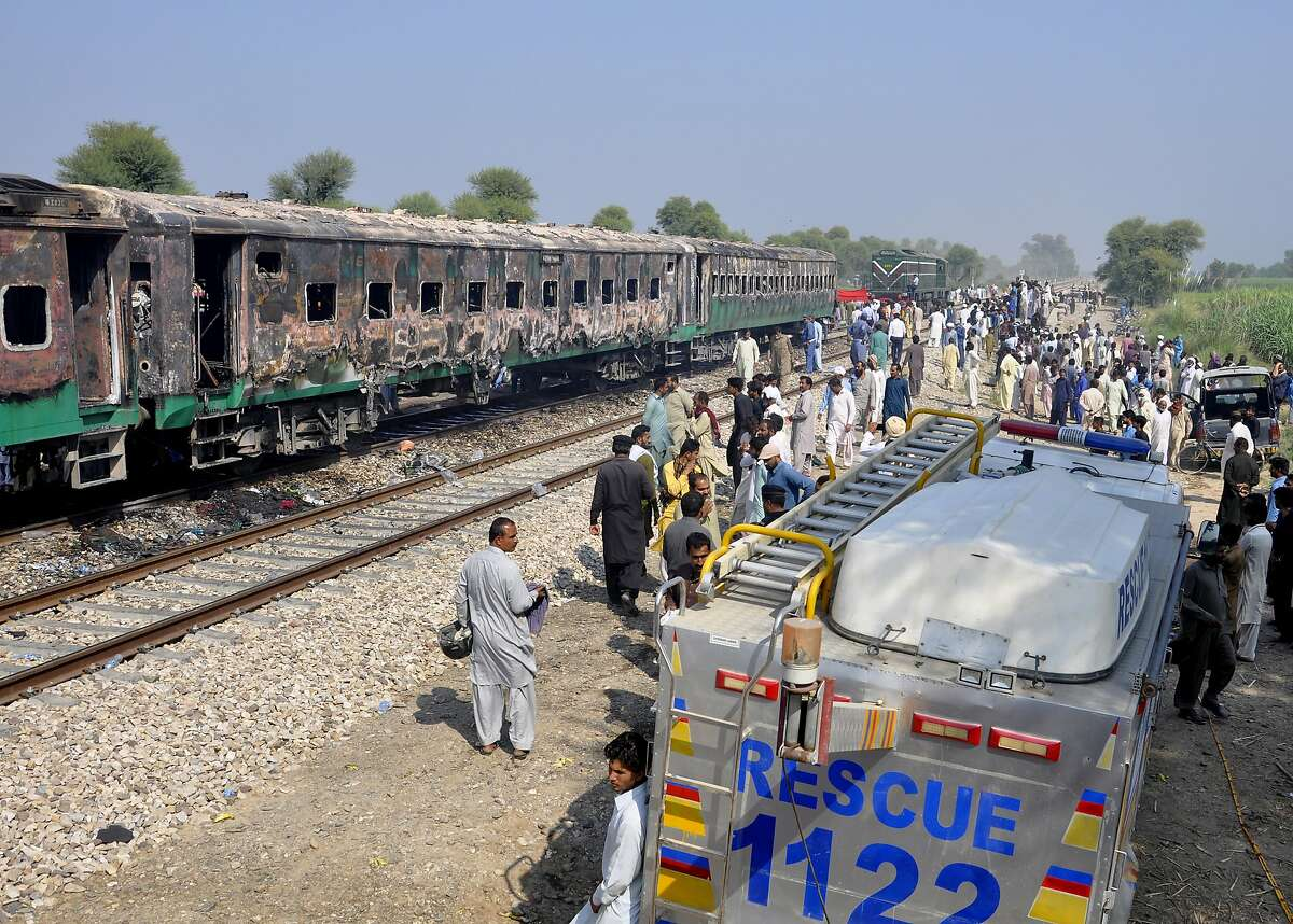 Soldiers and officials examine a damaged train in Liaquatpur, Pakistan. A massive fire engulfed three carriages. Survivors said it took nearly 20 minutes for the train to stop.