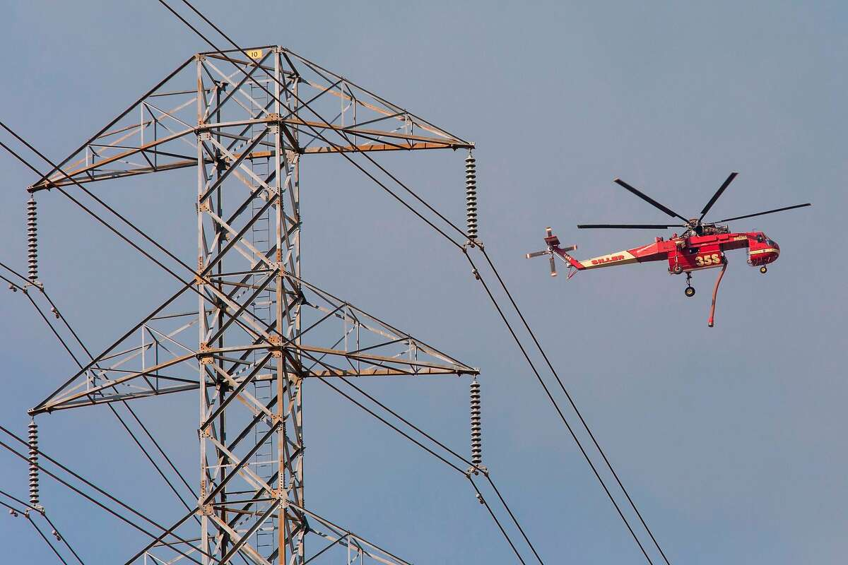 An helicopter flies past PG&E power lines en route to drop fire retardant during the Kincade Fire in Healdsburg on Oct. 26, 2019. The Sonoma County District Attorney's Office has initiated criminal proceedings against Pacific Gas and Electric for its role in causing the fire.
