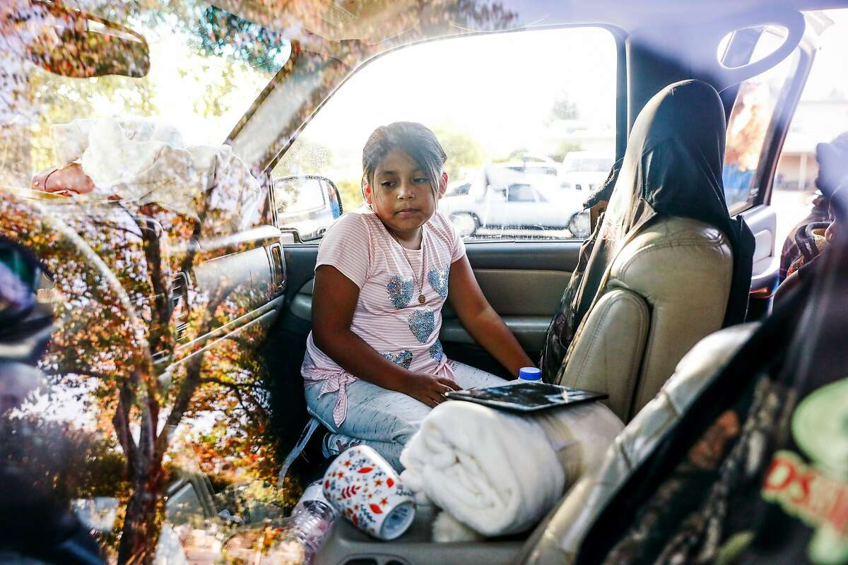 Kimberly Miguel, 9, the daughter of migrant workers, sits in the car that she and her family of eight have been sleeping in for the last six days following the evacuation orders from the Kincade fire at the Cloverdale Citrus Fairgrounds in Cloverdale, California, on Wednesday, Oct. 30, 2019.