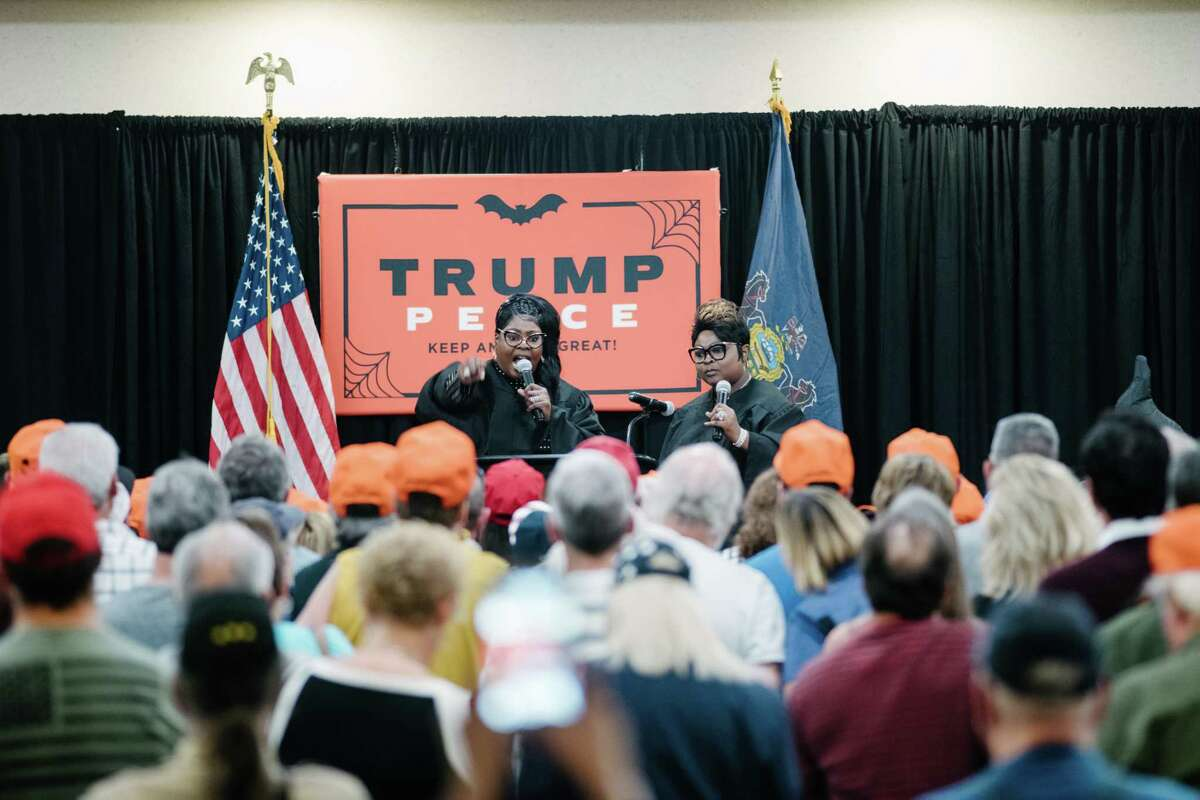 """Lynnette Hardaway, left, and Rochelle Richardson, popularly known as Diamond and Silk speak to attendees of the Trump campaign's """"Halloween Witch Hunt Party."""""""