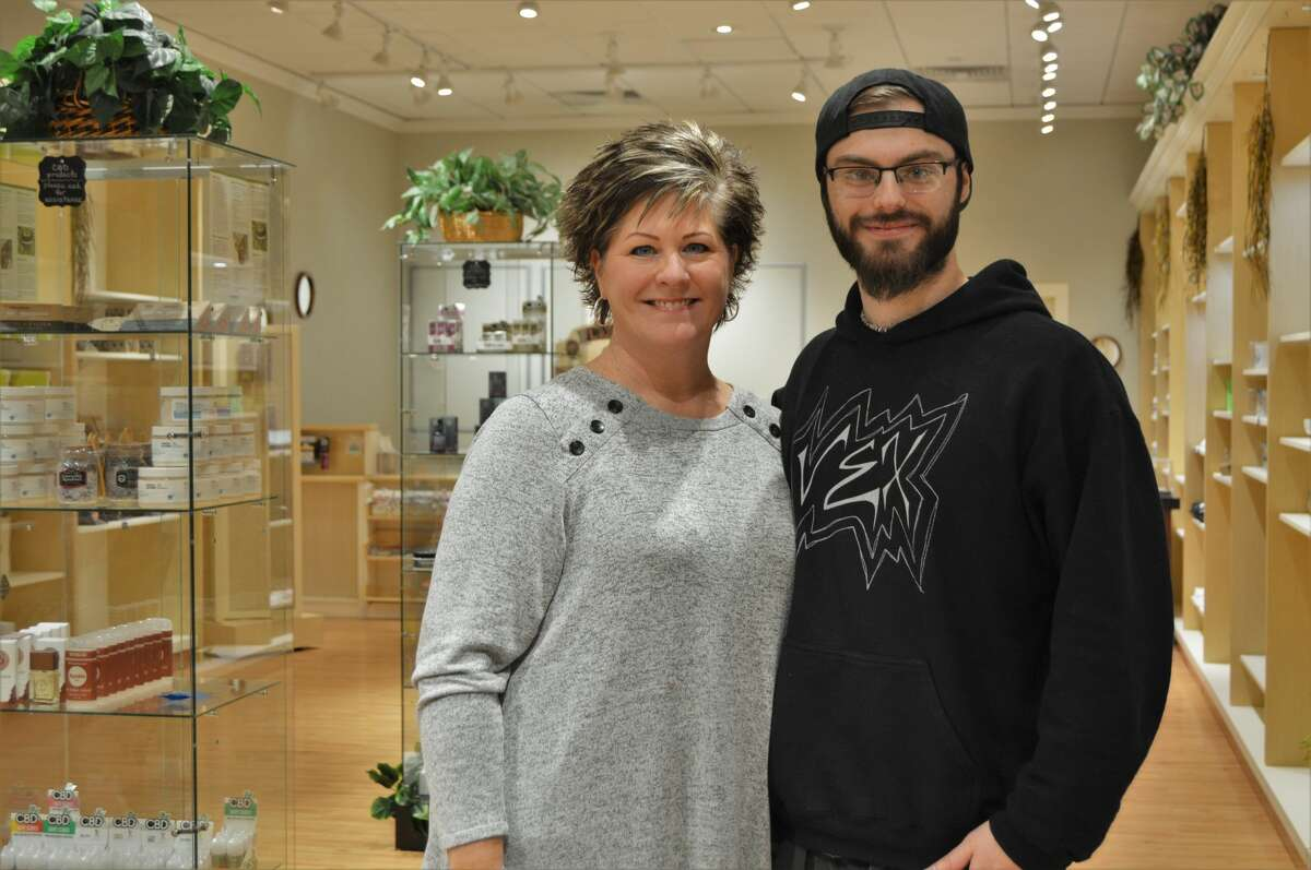Lisa Wiltse poses with her 21-year old son, Devin Dice in his new store, Outlife Collections, which opened on Oct. 3 in the Midland Mall. (Ashley Schafer/Ashley.Schafer@hearstnp.com)