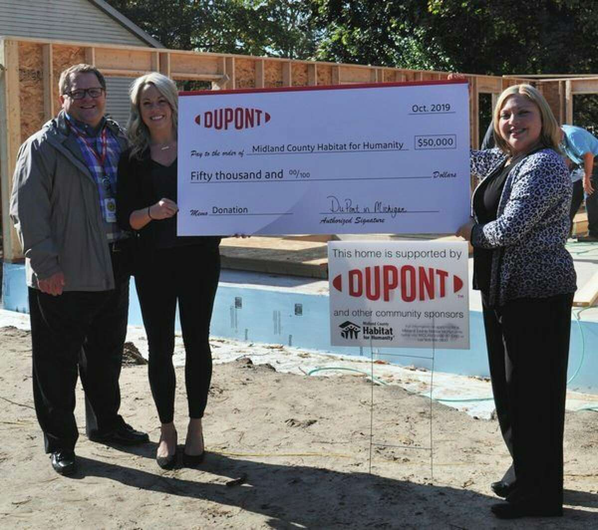 From left,Tim Lacey, DuPont Performance Building Solutions and Corian Design global vice president and general manager; Kayley Lyons, DuPont Community Relations and Internal Communications manager; and Jennifer Chappel, Midland County Habitat for Humanity CEO and president, pose for a photo to honor DuPont's awarding of a $50,000 grant to fund a Habitat building project. (Photo provided/Amanda King).