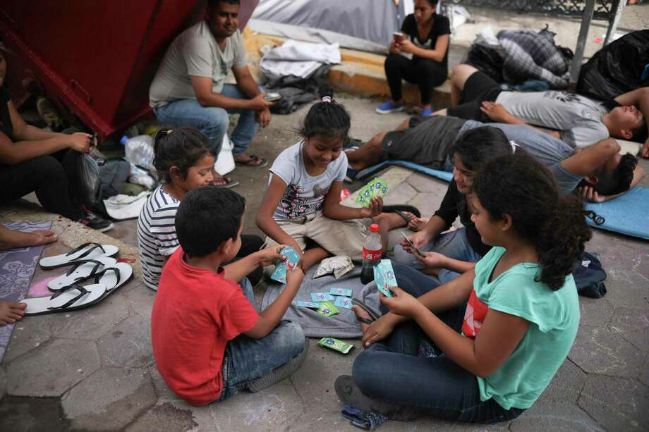 Young migrants play cards at an  encampment in Matamoros, Mexico, this summer. These children should be in safe schools, a reader says, not in harm's way. Photo: Emilio Espejel /Associated Press / Copyright 2019 The Associated Press. All rights reserved
