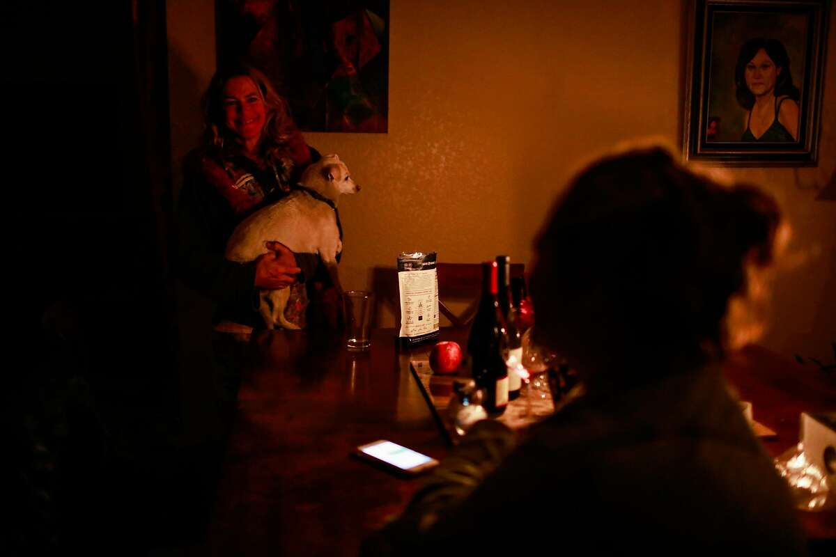 Jennifer Utsch (left) chats with friend Wanda Brester at her home which is lit by candles because they have no power following the Kincade Fire in Healdsburg, California, on Monday, Oct. 28, 2019. Wanda runs a motel and Jennifer is staying there because she was evacuated.
