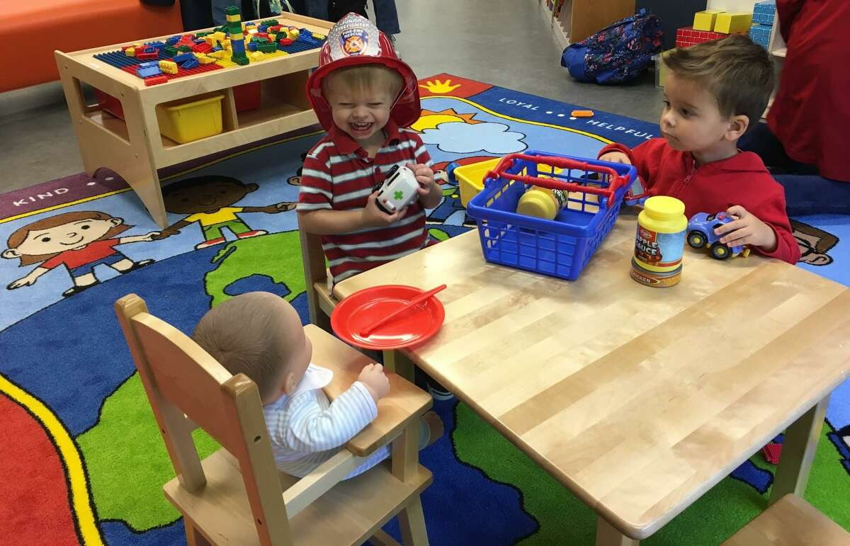 Michael Stanley, 2, center, shares a table at the George and Barbara Bush Family Place on Oct. 31 at the Maud Marks Library, with Kai Pretorius, 21/2.
