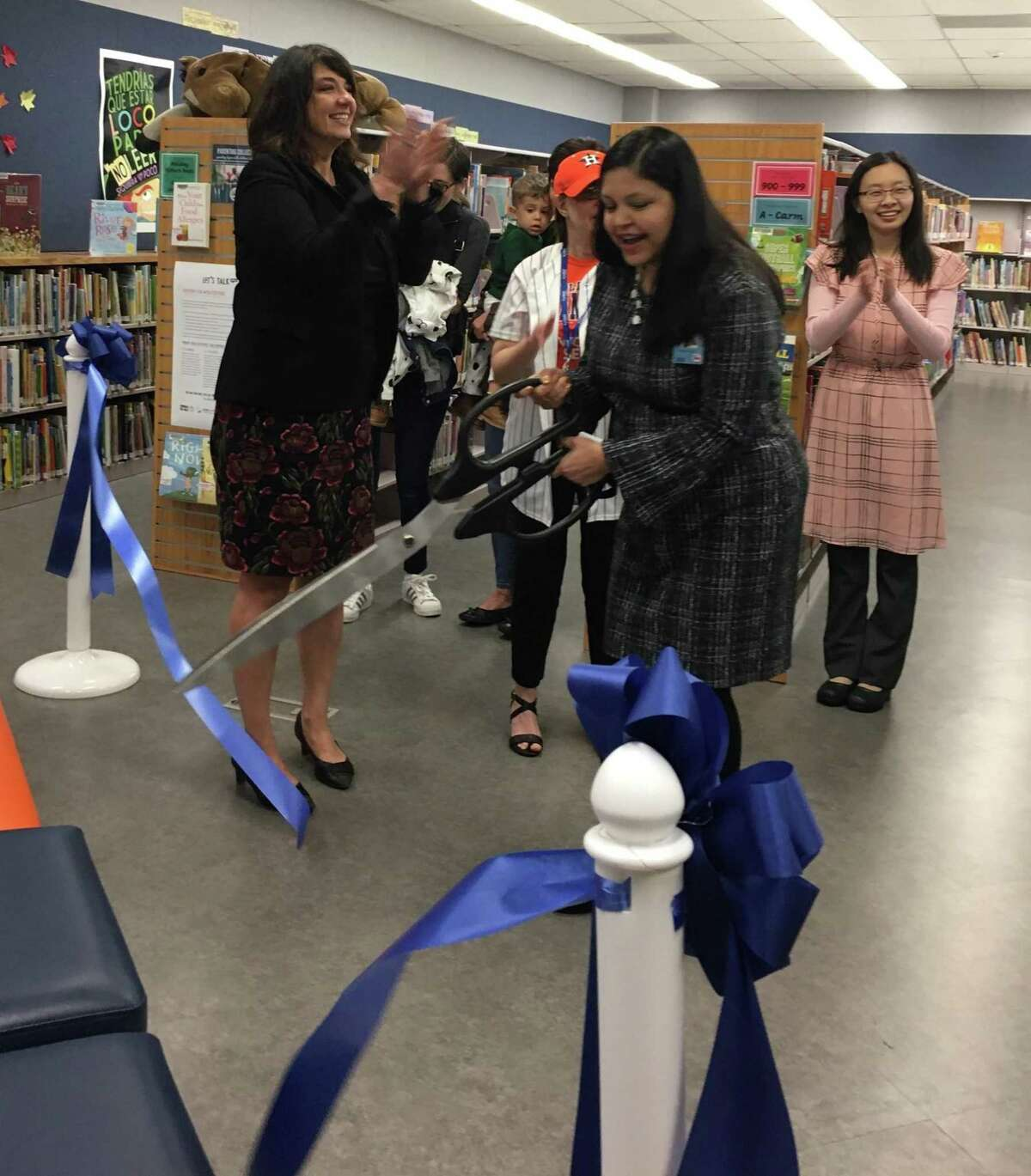 Akhila Bhat, branch manager of Maud Marks Branch Library, cuts the ribbon Oct. 31 of the library's George and Barbara Bush Family Place, one of eight in the Harris County Public Library system. Bhat spoke about family place prior to the ribbon cutting as did Jennifer Schwartz, left, program services manager for the Harris County Public Library.