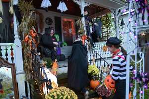 Trick-or-treaters get candy from Debbie Mapes, left, who is sitting on the deck of her house decked out in Halloween decorations on Thursday, Oct. 31, 2019 in Greenwich, N.Y. (Lori Van Buren/Times Union)