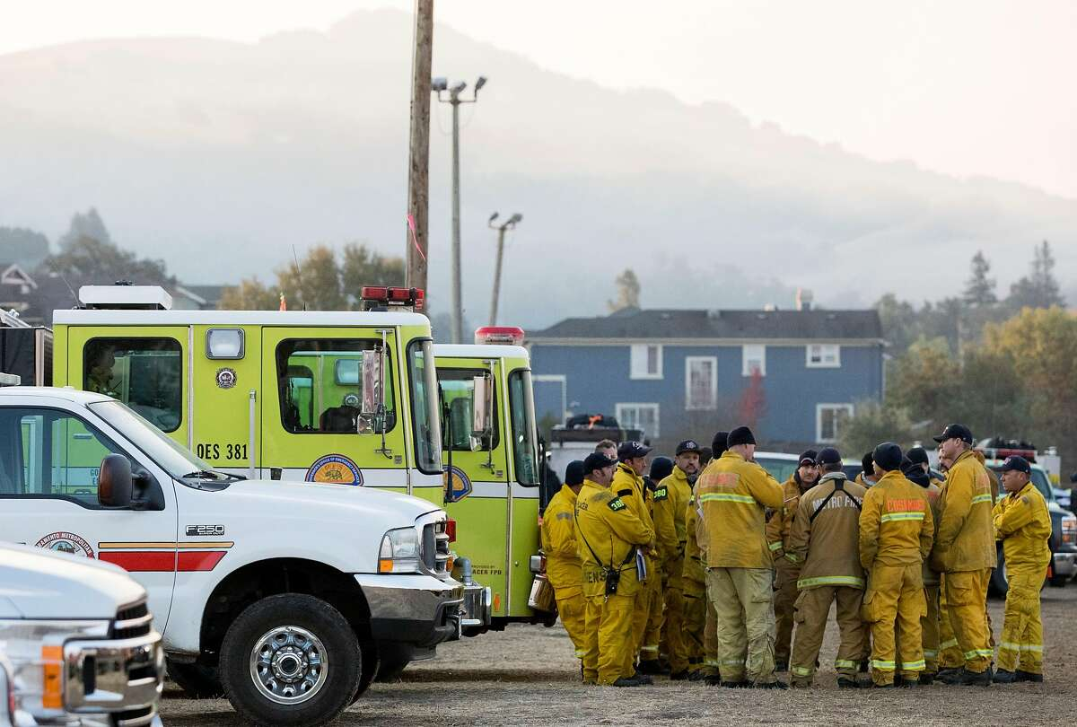 Firefighters huddle up to plan their day before heading out from the Kincade Fire incident base at the Sonoma County Fairgrounds in Santa Rosa, Calif. Tuesday, Oct. 29, 2019.