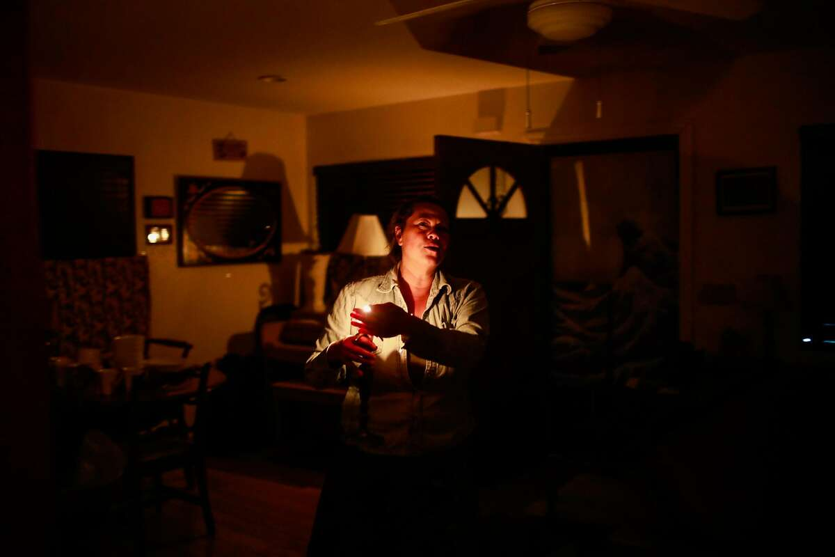 Wanda Brester, who owns the L&M Motel walks through her house by candlelight in Healdsburg, California, on Monday, Oct. 28, 2019.