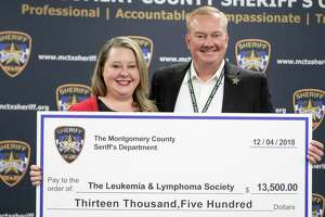 "Mindy Reynolds, Leukemia & Lymphoma Society campaign manager, accepts a $13,500 check from Montgomery County sheriff Rand Henderson. The money was raised through donations during ""No Shave November."""