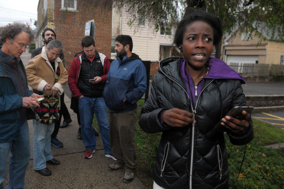 Surrounded by supporters outside the Derby courthouse, Shaundrece Beckford speaks on a cellphone with her husband, Domar Shearer, shortly before he was safely escorted to a waiting vehicle after spending most of the day sheltered in the public defender's office to avoid being detained by Federal immigration agents in Derby, Conn. Oct. 31, 2019. Photo: Ned Gerard, Hearst Connecticut Media / Connecticut Post