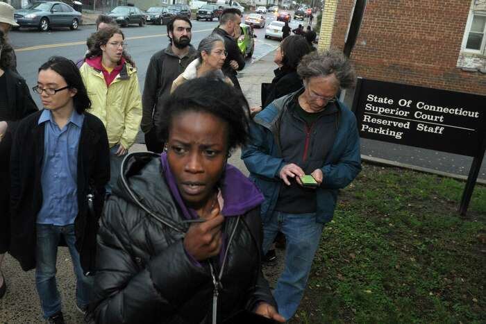 Outside the Derby courthouse, Shaundrece Beckford speaks on a cellphone with her husband, Domar Shearer, who sheltered in the public defender's office to avoid being detained by Federal immigration agents Oct. 31, 2019. Edward Finlayson, a judicial marshal who authorities claim assisted Shearer in avoiding apprehension by ICE agents, was fired in December 2019.