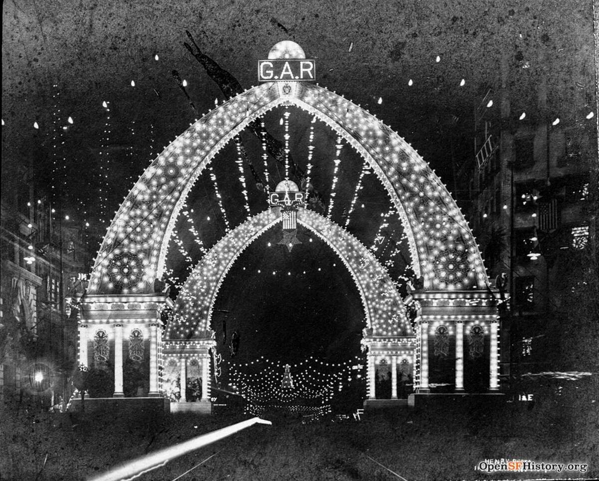 A night view of the Grand Army of the Republic arch over Market Street in San Francisco. This one was erected for a later National Encampment held in the early 1900s. The Examiner Building is at right, Ferry Building in distance.