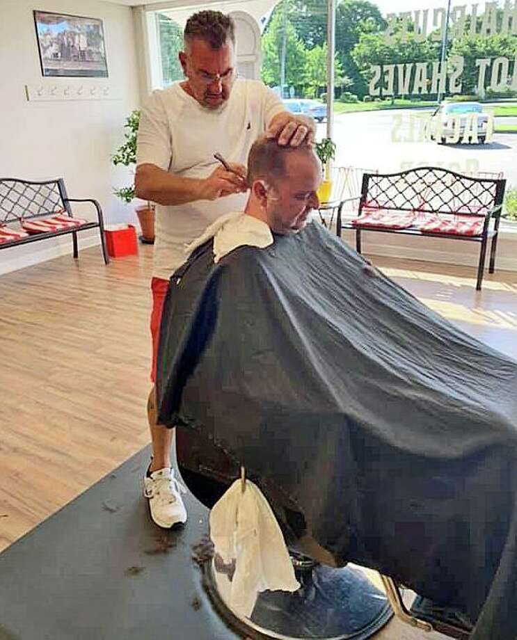 Barber Kevin Shea cuts a customer's hair at Kevin Edward Gentleman's Barber Shop where free haircuts are being offered to veterans their families on Veteran's Day. Photo: Contributed Photo