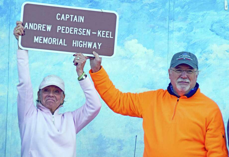 Helen Pedersen-Keiser, along with her husband, Bob Pedersen-Keiser, holds the sign that designates a portion of Route 79 in Madison renamed for her son, U.S. Army Special Forces Capt. Andrew Pedersen-Keel, killed in action, in Afghanistan on March 11, 2013. Photo: Contributed Photo /