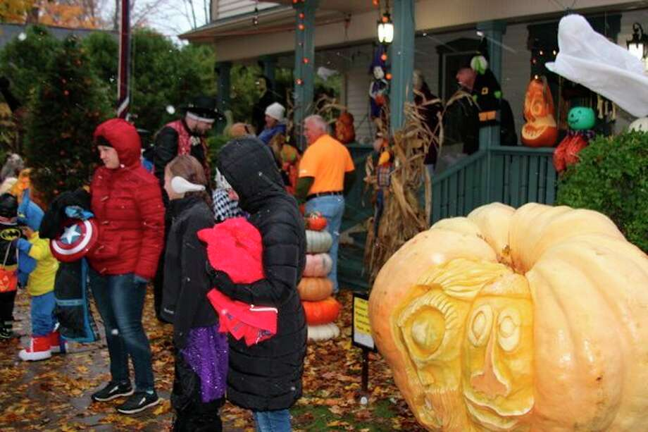 Visitors brave the cold and snow on Halloween to check out Ed Moody's Halloween display, which included colossal carved pumpkins. (Photo/Colin Merry)