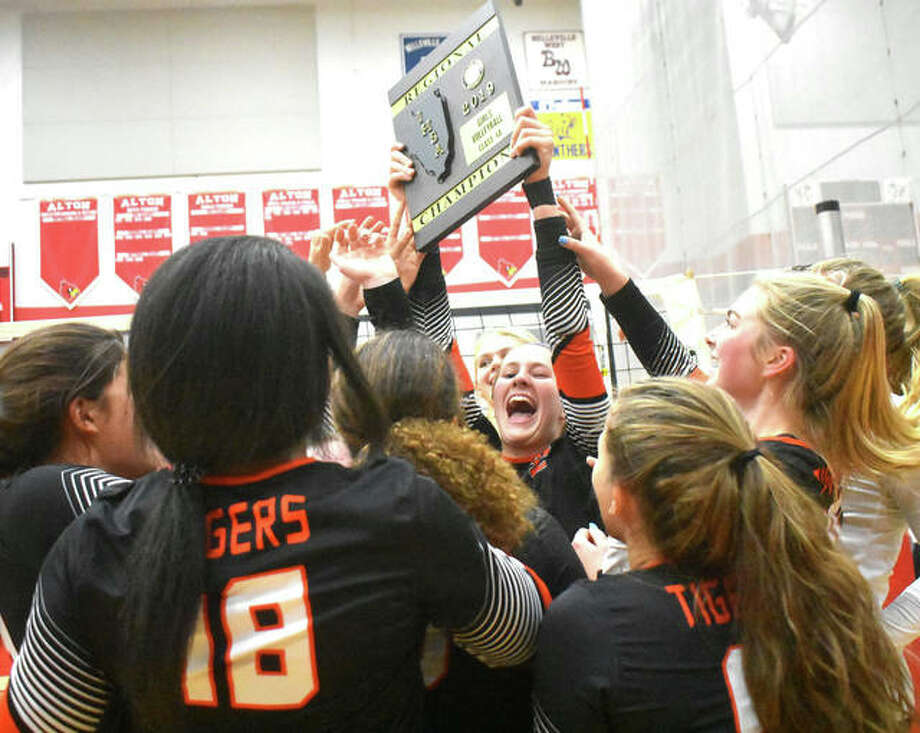 Edwardsville senior Maddie Isringhausen (middle) holds up the regional championship for teammates to celebrate Thursday night at the Alton Class 4A Regional in Godfrey. Photo: Matt Kamp / Hearst Midwest