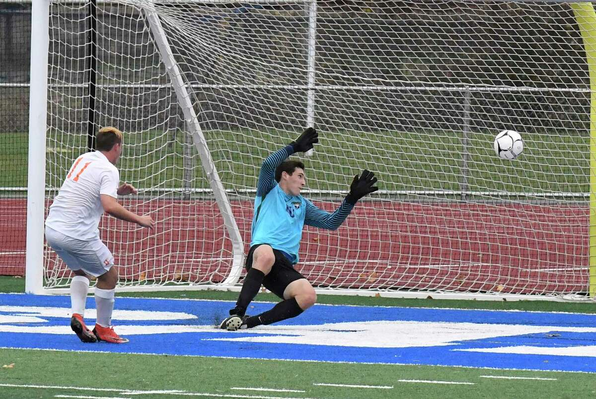 Bethlehem's Aiden McCaffrey ,left, scores against Christian Brothers Academy goalkeeper Dan Kelly during a Section II Class AA boys' soccer semifinal game in Troy, N.Y., Thursday, Oct. 31, 2019. Bethlehem won the game 1-0. (Hans Pennink / Special to the Times Union)
