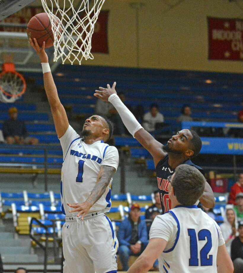 Wayland Baptist's Tre Filmore goes in for the layup in front of Arlington Baptist defender Jordan Williams as teammate Reese Puckett looks in a men's basketball game on Thursday night in the Hutcherson Center. Photo: Nathan Giese/Planview Herald