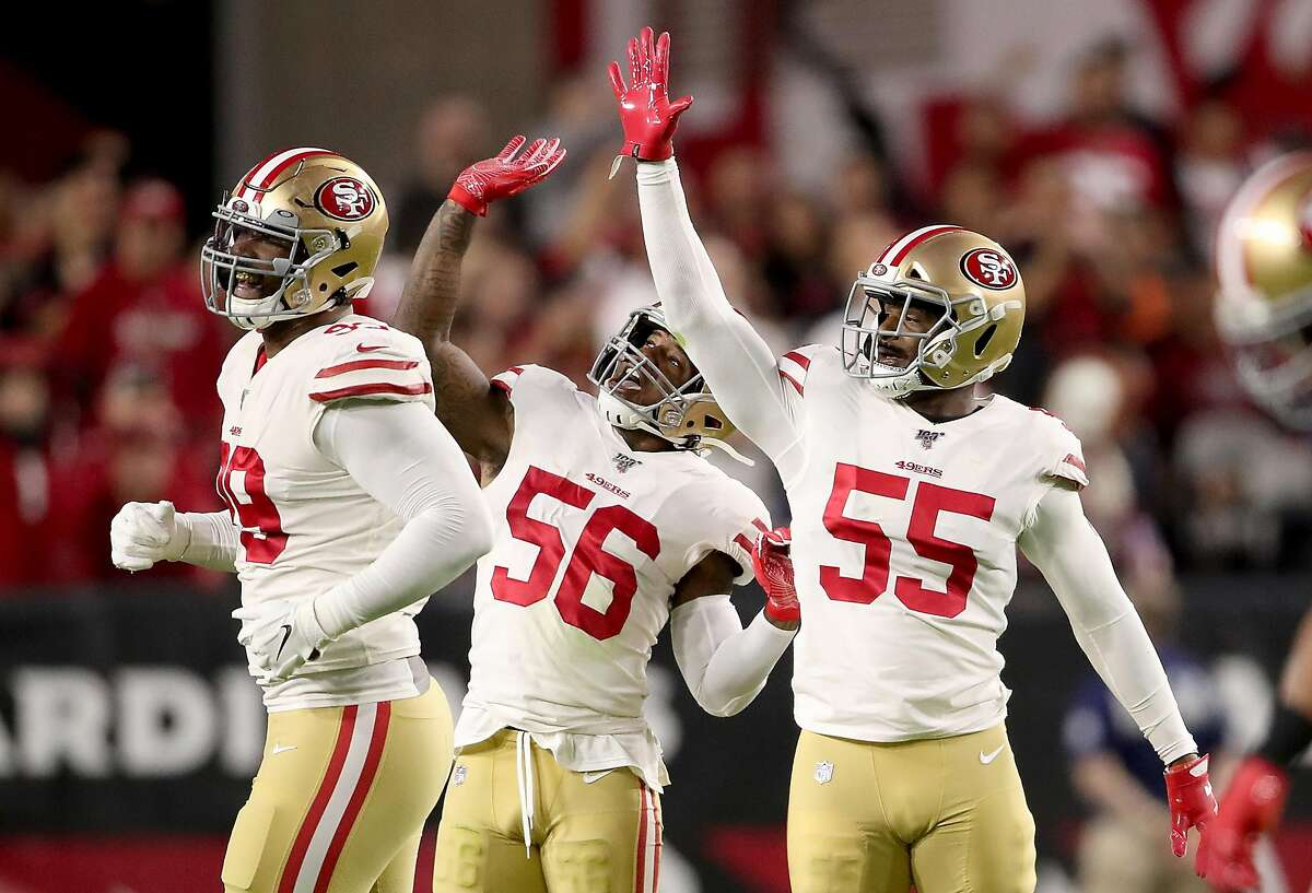 Defensive end Dee Ford #55 , middle linebacker Kwon Alexander #56 and defensive tackle DeForest Buckner #99 of the San Francisco 49ers celebrate a sack during the game against the Arizona Cardinals at State Farm Stadium on