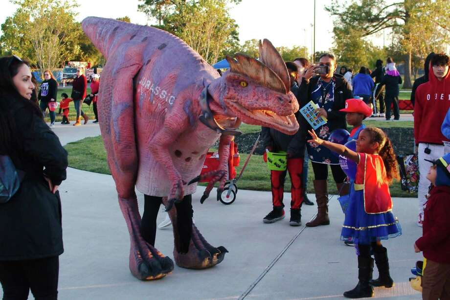 A costumed dinosaur greets costumed youngsters walking the Trick or Treat Trail at Independence Park on Halloween night in Pearland. Photo: Kirk Sides