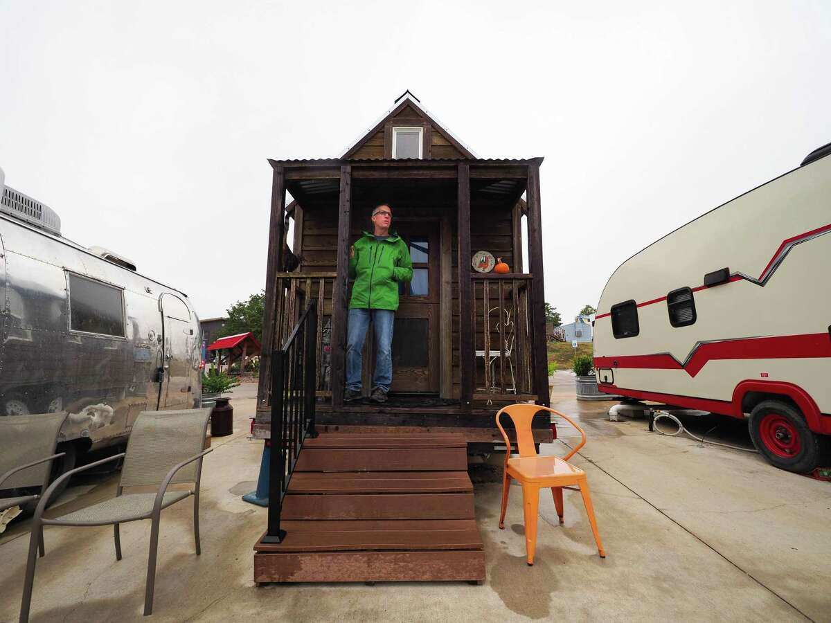 Chris LeBlanc stands on the back porch of the Ruby unit at the Community Inn. The tiny house is decorated with a Wizard of Oz motif.