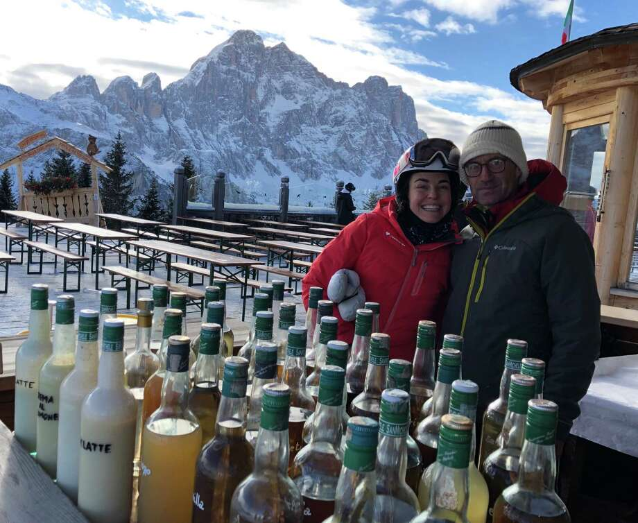 With the jagged spires of the Dolomites as a backdrop, the author, left, pauses on a guided inn-to-inn ski trip in Italy to try locally brewed grappa in Col dei Baldi. Photo: Courtesy Of Amy Tara Koch / Courtesy of Amy Tara Koch