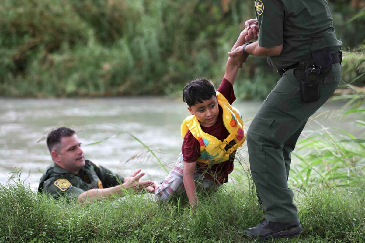 Border Patrol Agent in Charge Eagle Pass, Bryan Kemmett, left, passes a seven year old boy from Honduras to another agent after he was rescued from the swollen Rio Grande River. Agents responded to three rafts crossing the river in Eagle Pass, on Friday, May 10, 2019. A total of 9 were helped out of the river.