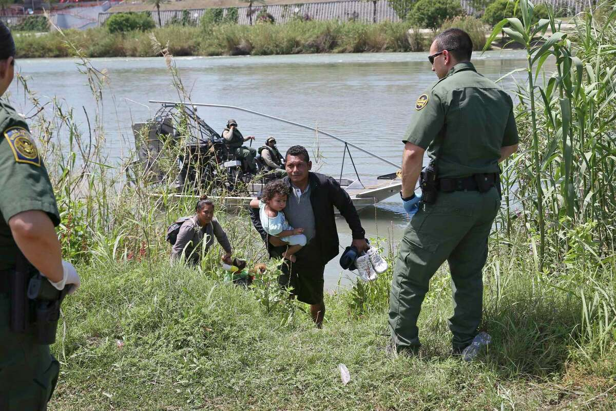 After wading across the Rio Grande at Eagle Pass, Texas, a Central American migrant family turns themselves into U.S. Border Patrol agents, Thursday, April 4, 2019. Central American families and children apprehension have increase sharply throughout the Southwest region.
