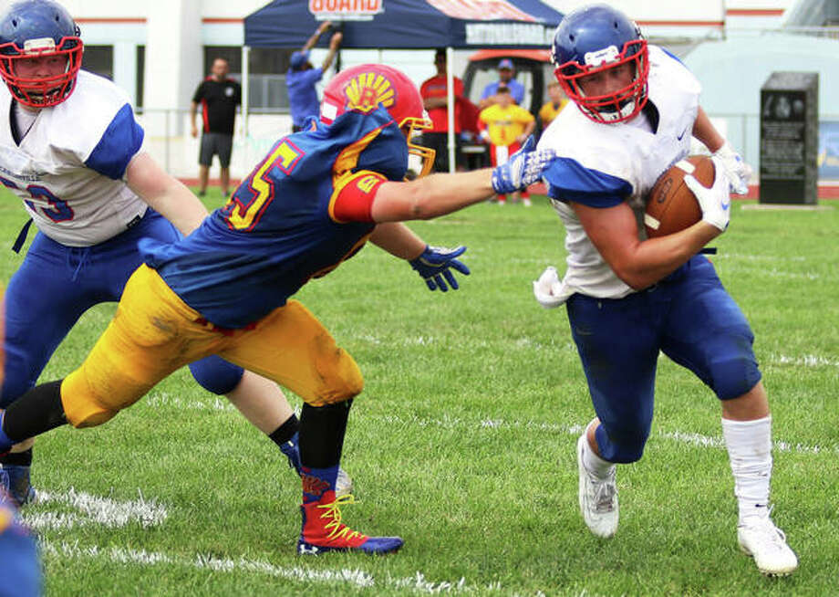 Carlinville running back Colton DeLong (right) gets around Roxana linebacker David Pluester in a Week 1 game at Raich Field in Roxana. Both the Cavaliers and Roxana open the playoffs on the road Saturday, with Carlinville at Mount Carmel in Class 3A and Roxana at Columbia in Class 4A. Photo: Greg Shashack / The Telegraph