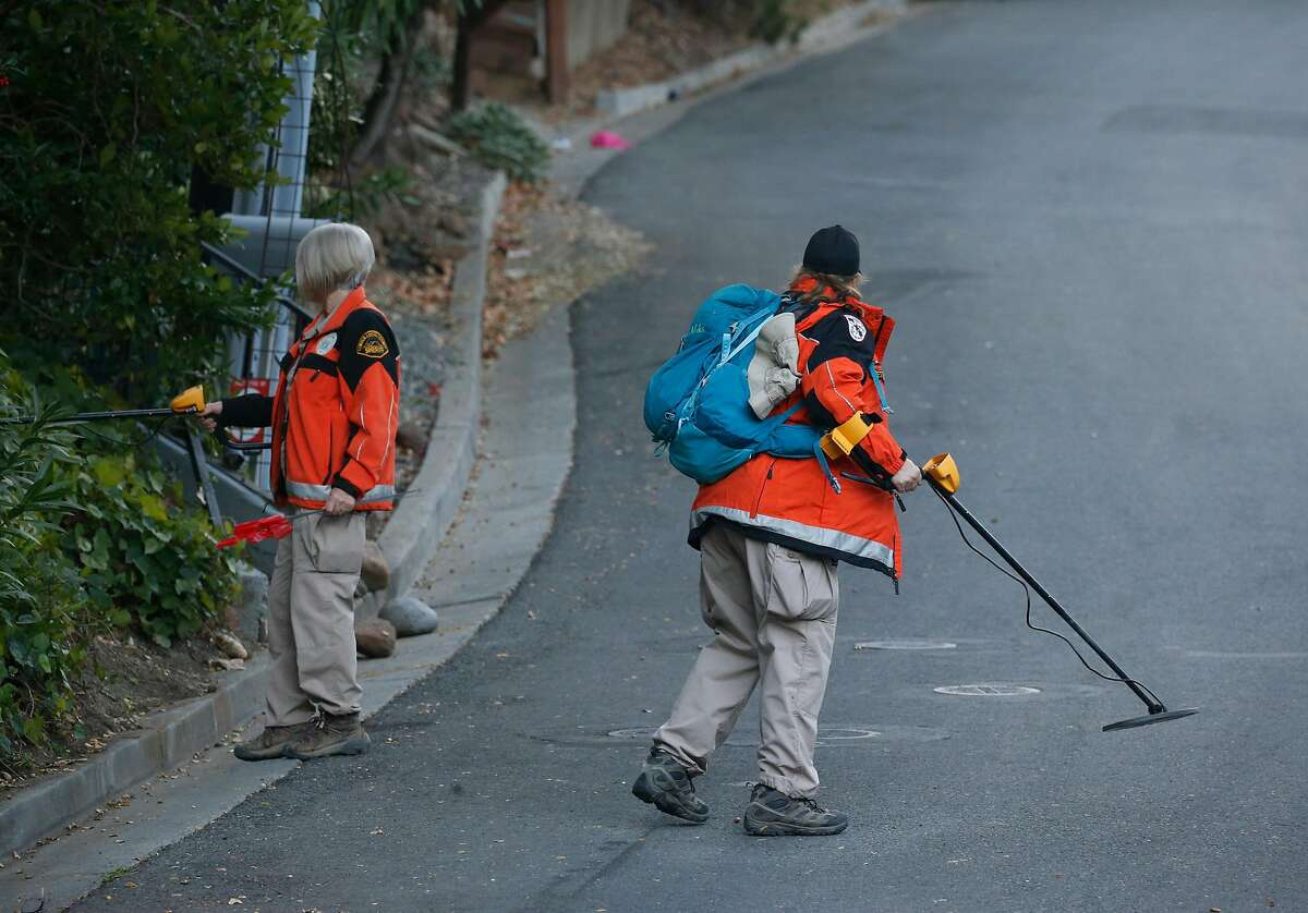 Members of the Contra Costa County Search and Rescue team use metal detectors to look for evidence on Knickerbocker Lane near Lucille Way in Orinda, Calif. on Friday, Nov. 1, 2019 after four people were killed and several left injured in a shooting during a Halloween party Thursday night.