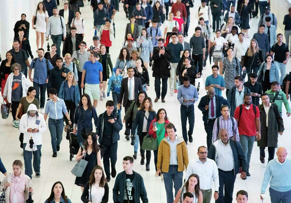 FILE - In this June 21, 2019, file photo, commuters walk through a corridor in the World Trade Center Transportation Hub, in New York. The United States will add 79 million people in the next 40 years, but growth will slow as the U.S population gets older, according to new projections presented Thursday at a meeting of demographers.