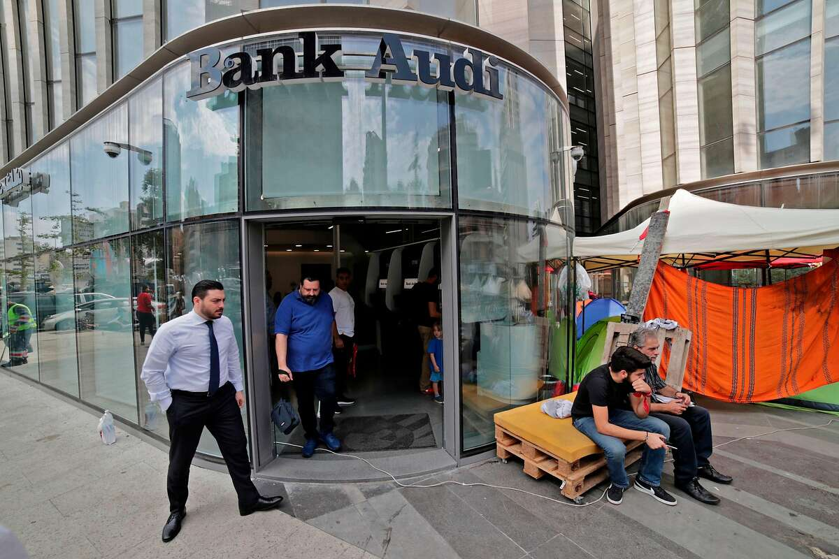 Lebanese protesters camp at the entrance of a bank in Beirut on November 1, 2019. - Lebanon banks reopened for the first time in two weeks today as the country began to return to normal following mass demonstrations for radical political change. The unprecedented popular push to remove a political class seen as corrupt, incompetent and sectarian, had kept the country on lockdown since October 17.