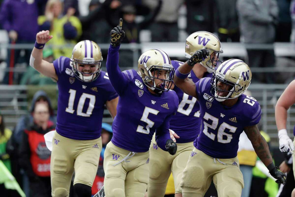 Washington's Andre Baccellia (5) celebrates his five-yard touchdown reception against Oregon with Jacob Eason (10), Cade Otton and Salvon Ahmed (26) in the first half of an NCAA college football game Saturday, Oct. 19, 2019, in Seattle.