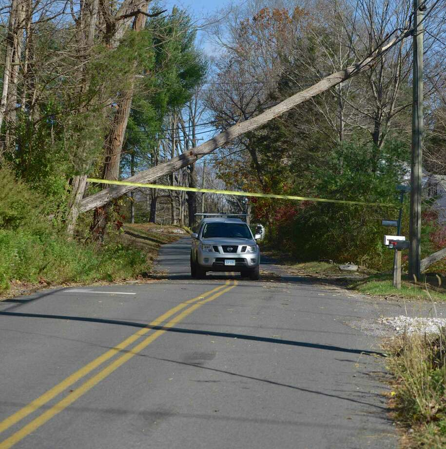 A truck drives under a tree leaning on a power line on South Kent Road in Gaylordsville on Friday morning.Winds gusting to more than 50 mph have knocked downed trees, leaving thousands without power in the area. November 1, 2019, in New Milford, Conn. Photo: H John Voorhees III / Hearst Connecticut Media / The News-Times